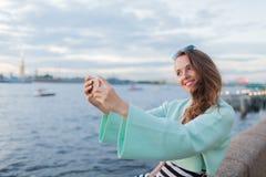 年轻和美丽的女孩坐河的堤防 她看日落和采取在您的电话的一selfie 圣徒 免版税库存照片