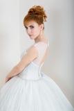 年轻和美丽的红头发人新娘穿戴了摆在演播室的婚礼礼服 免版税库存照片