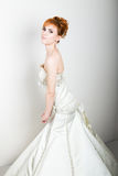 年轻和美丽的红头发人新娘穿戴了摆在演播室的婚礼礼服 库存照片