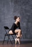 年轻和美丽的芭蕾舞女演员坐在点鞋子的一把椅子 免版税库存照片