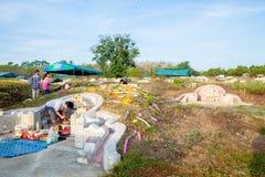 年轻和老在祖先前祈祷,祭扫坟茔对 图库摄影