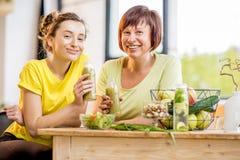 年轻和老妇人用户内健康食物 免版税图库摄影