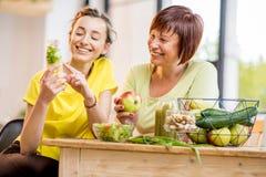 年轻和老妇人用户内健康食物 免版税库存图片
