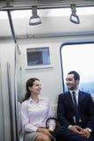 和聊天坐地铁的两个年轻商人 库存图片