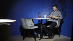 和聊天由手机的年轻人坐酒吧,工作,抽烟的e香烟vape 股票录像