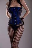 黑和蓝色束腰的性感的滑稽的妇女 库存照片