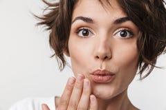 和蔼可亲的妇女画象有短的棕色头发的在盖她的嘴的基本的T恤杉用手 免版税图库摄影