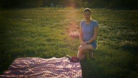 和观看入照相机的女孩坐草坪 影视素材