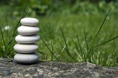 和谐和平衡,简单的小卵石在草,朴素,五块石头耸立 图库摄影