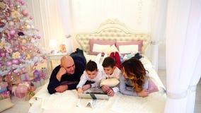 和谐家庭获得乐趣和一起观看在计算机上的动画片,说谎在床上在有圣诞树的明亮的卧室 股票录像