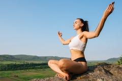 和谐的片刻 美丽的坚强的深色的在岩石和放松的女子实践的瑜伽 库存照片