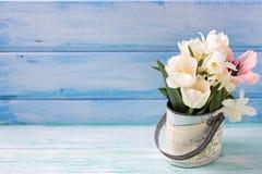 黄水仙和郁金香在绿松石pai的葡萄酒碗开花 免版税库存图片