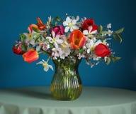 黄水仙和郁金香花束在桌上 免版税图库摄影