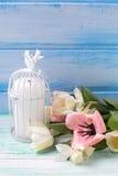 黄水仙和郁金香花,在绿松石的蜡烛绘了木头 库存照片