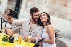 和采取selfie的游人坐在咖啡馆,饮用的咖啡 库存图片