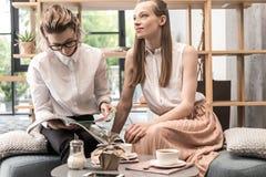 和读杂志的女同性恋的夫妇一起坐,饮用的咖啡 免版税库存照片