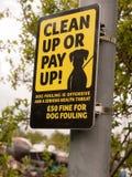 黑和黄色标志外面在杆说清扫或支付  免版税图库摄影