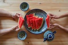 年轻和年长妇女用西瓜在他的手上在一个亚洲咖啡馆,撒马而罕,乌兹别克斯坦 免版税库存图片