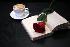 咖啡、一朵红色玫瑰和一本书在桌上 库存照片