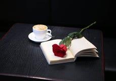 咖啡、一朵红色玫瑰和一本书在桌上 免版税库存图片