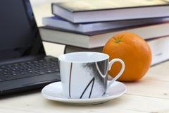 咖啡、书、膝上型计算机和桔子 库存照片