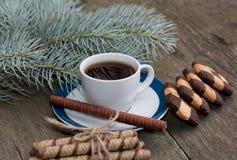 咖啡、冷杉木分支和两个小组美丽的曲奇饼 免版税库存照片