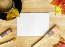 咖啡、刷子、白皮书和秋叶在木背景 免版税图库摄影