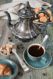 咖啡、咖啡罐和新月形面包 免版税库存照片