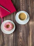 咖啡、多福饼和桃红色笔记薄在木背景 免版税库存图片