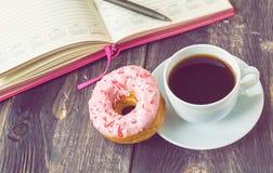 咖啡、多福饼和笔记薄在木背景 库存照片