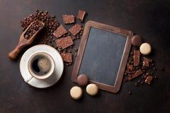 咖啡、巧克力和蛋白杏仁饼干在老厨房用桌上 库存图片