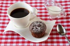咖啡、巧克力松饼用搽粉的糖和牛奶在一个调味汁瓶在一张红色白色方格的桌布 免版税库存图片