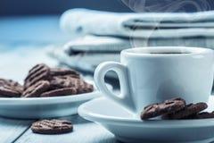 咖啡、巧克力饼干和背景报纸 免版税图库摄影