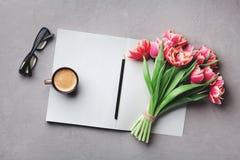 咖啡、干净的笔记本、镜片和美丽的花在石台式视图在舱内甲板放置样式 妇女运转的书桌 免版税库存图片
