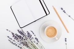 咖啡、干净的笔记本和淡紫色在白色背景从上面开花 妇女运转的书桌 舒适早餐大模型 平的位置 免版税库存照片
