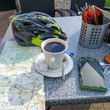 咖啡、循环的盔甲、地图和太阳充电器在室外 库存照片