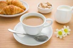 咖啡、新月形面包、牛奶罐和糖在桌上 免版税库存照片