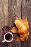 咖啡、新月形面包和秋叶 免版税库存照片