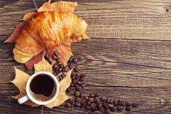 咖啡、新月形面包和秋叶 免版税库存图片