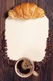 咖啡、新月形面包和纸 图库摄影