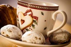 咖啡、曲奇饼、一个新月形面包和圣诞节开花 免版税库存照片