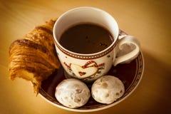 咖啡、曲奇饼、一个新月形面包和圣诞节开花 库存图片