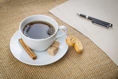咖啡、曲奇饼、笔和纸在麻袋布背景 免版税库存照片