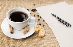咖啡、曲奇饼、笔和纸在麻袋布背景 库存图片