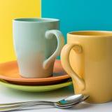 咖啡、板材和一把匙子的两个空的陶瓷杯子在与空间的蓝色和黄色背景您的文本的 库存照片