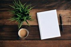 咖啡、玻璃笔、绿色植物和空的笔记本在木桌上 库存照片