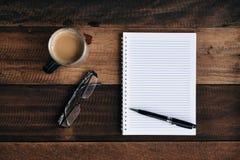 咖啡、玻璃笔和空的笔记本在木桌上 免版税库存照片