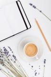 咖啡、空的笔记本和淡紫色在白色背景从上面开花 妇女运转的书桌 舒适早餐大模型 平的位置 库存照片
