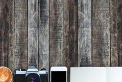 咖啡、笔记本、移动电话和照相机在老木纹理背景 免版税图库摄影