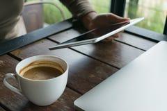 咖啡、膝上型计算机和笔记薄在桌上在咖啡馆 库存照片